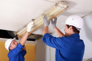 Two electrician repairing office lighting